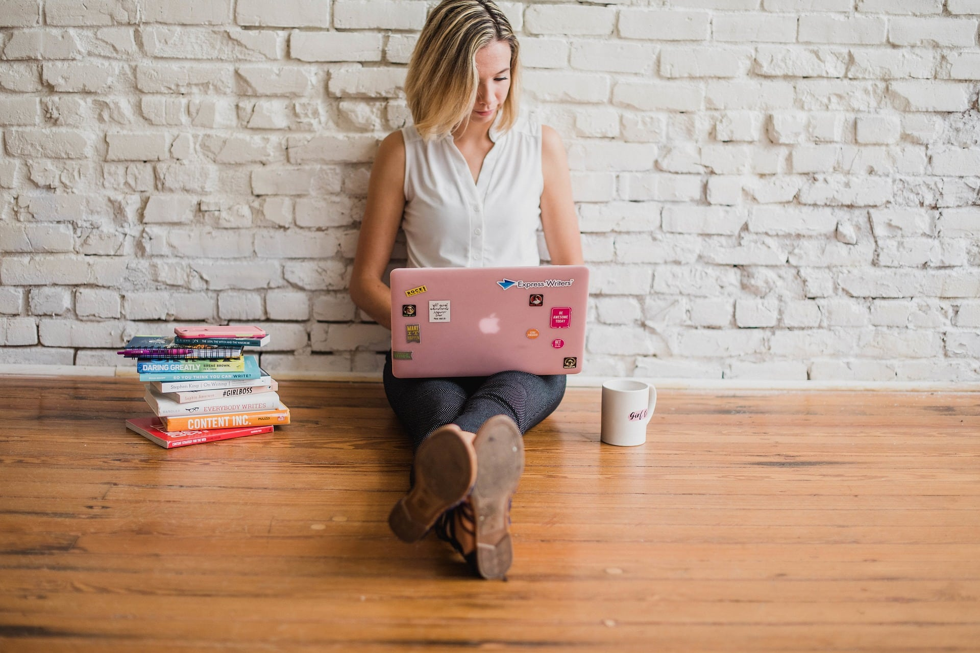 A woman with a laptop sits against a white brick wall with a cup of coffee and a stack of books.