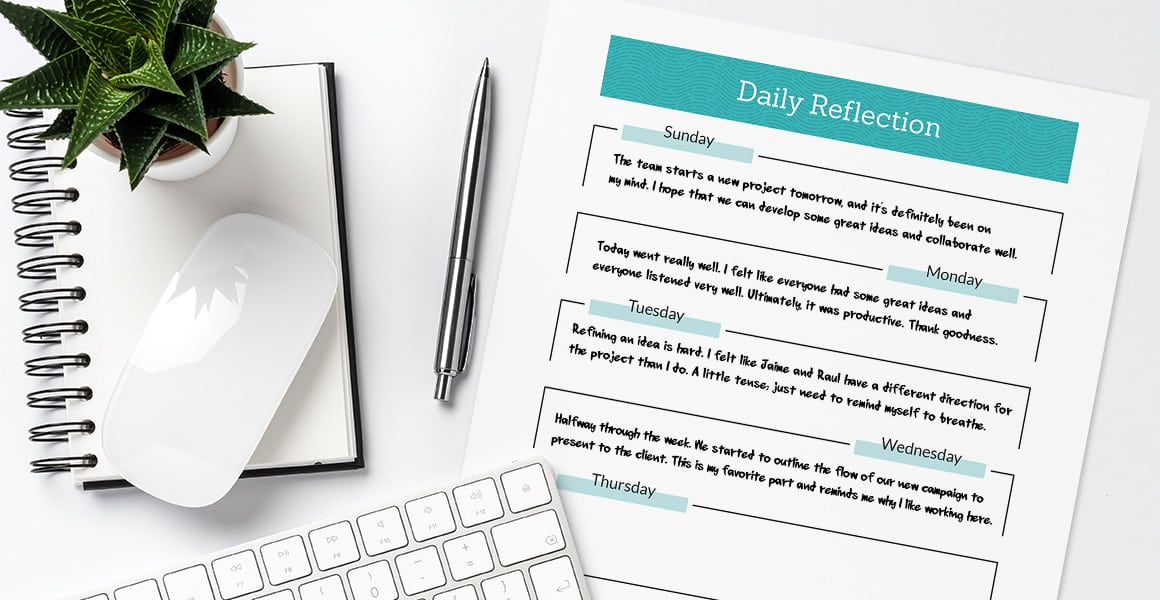 daily reflection sheet on white background with a journal, plant, pen, mouse, and keyboard.